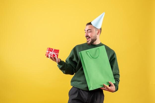 Vue de face jeune homme tenant peu de cadeau sur fond jaune