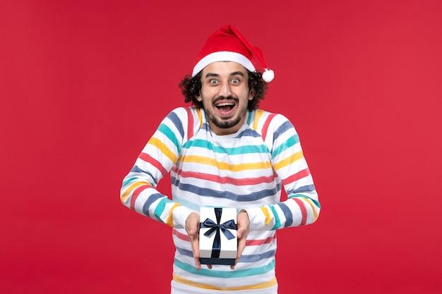 Vue de face jeune homme tenant peu de cadeau sur le mur rouge émotion rouge vacances nouvel an