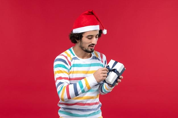 Vue de face jeune homme tenant peu de cadeau sur le mur rouge émotion vacances nouvel an rouge
