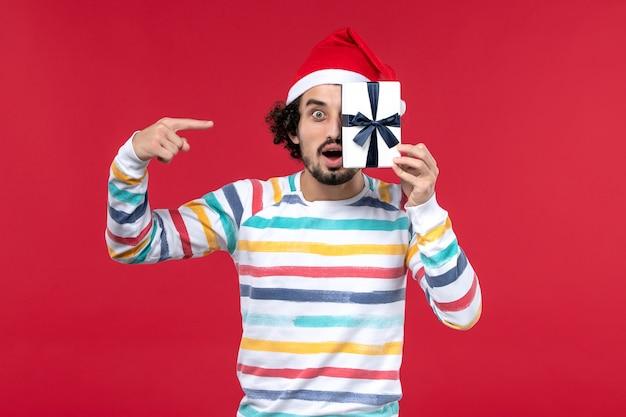 Vue de face jeune homme tenant peu de cadeau sur le mur rouge nouvel an vacances émotion rouge