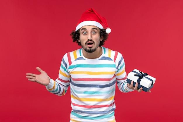 Vue de face jeune homme tenant peu de cadeau sur le mur rouge vacances nouvel an émotion