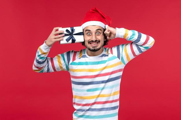 Vue de face jeune homme tenant peu de cadeau sur le mur rouge vacances nouvel an émotions rouge