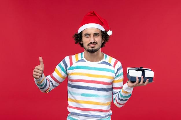 Vue de face jeune homme tenant peu de cadeau sur le mur rouge vacances nouvel an émotions
