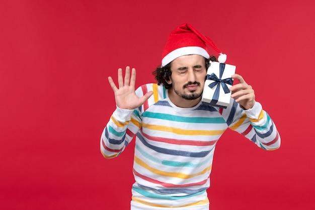 Vue de face jeune homme tenant peu de cadeau sur le plancher rouge émotion rouge vacances nouvel an