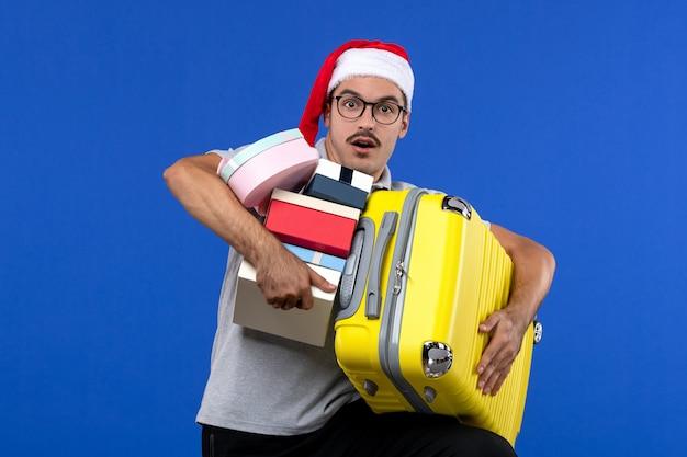 Vue de face jeune homme tenant présente avec sac sur fond bleu avions vols vacances