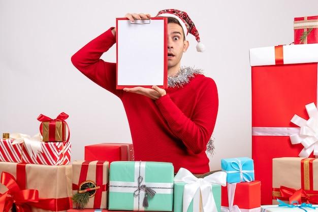 Vue de face jeune homme tenant le presse-papiers assis autour de cadeaux de noël
