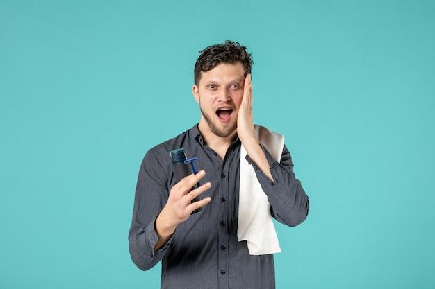 Vue de face jeune homme tenant un rasoir sur fond bleu