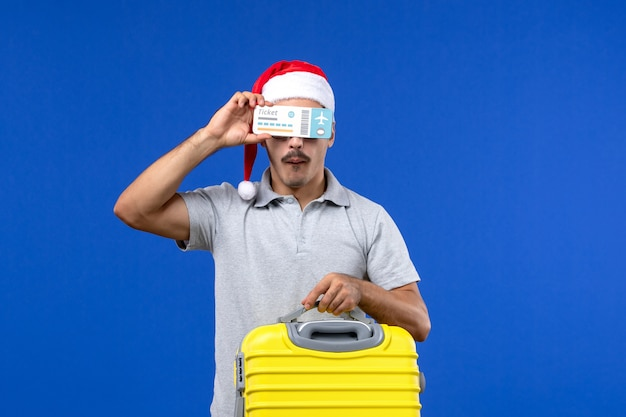 Vue de face jeune homme tenant un sac jaune et des billets sur des avions de vacances de vols de fond bleu