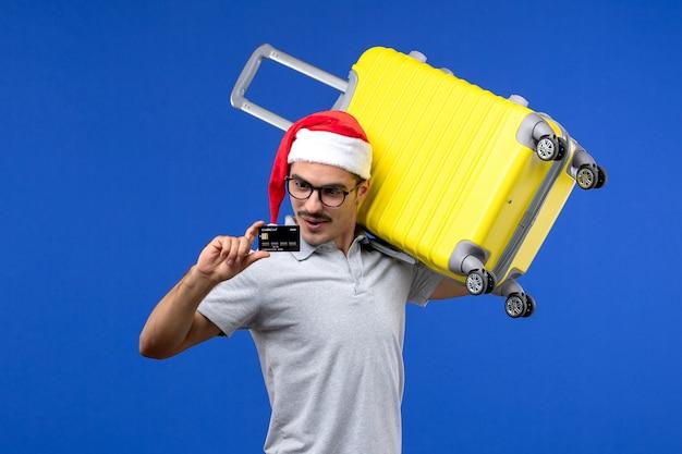 Vue de face jeune homme tenant un sac jaune et une carte bancaire sur un vol d'avion de vacances fond bleu