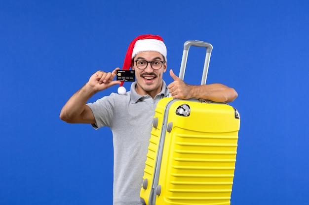 Vue de face jeune homme tenant un sac jaune et une carte bancaire sur le vol des avions de vacances fond bleu