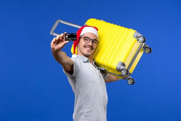 Vue de face jeune homme tenant un sac jaune et une carte bancaire sur des vols d'avion de vacances fond bleu