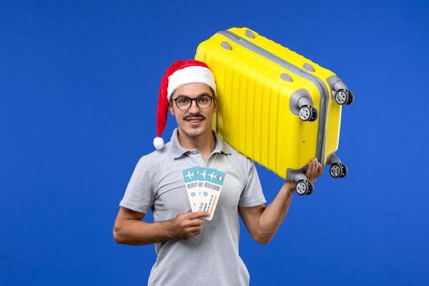 Vue de face jeune homme tenant un sac lourd et des billets sur des avions de vacances vol mur bleu