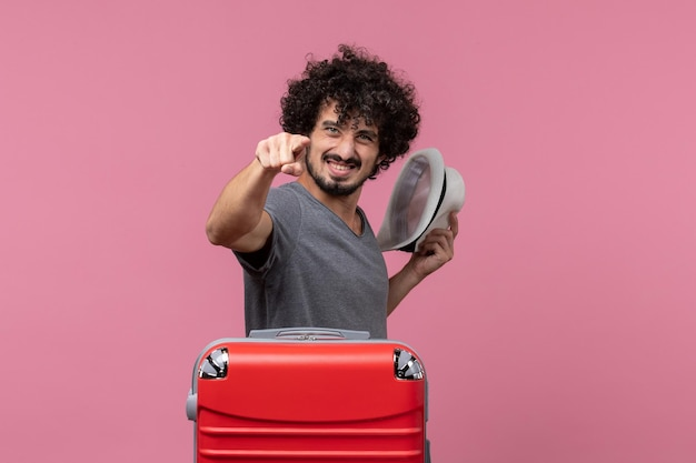 Vue de face jeune homme tenant son chapeau et se préparant pour des vacances sur un espace rose clair