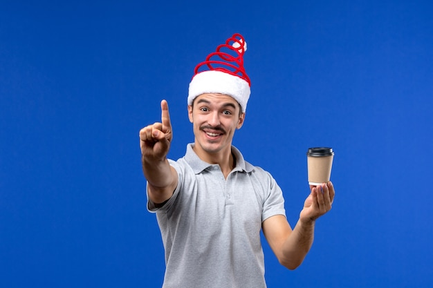 Vue de face jeune homme tenant une tasse de café sur le bureau bleu nouvel an mâle vacances émotions