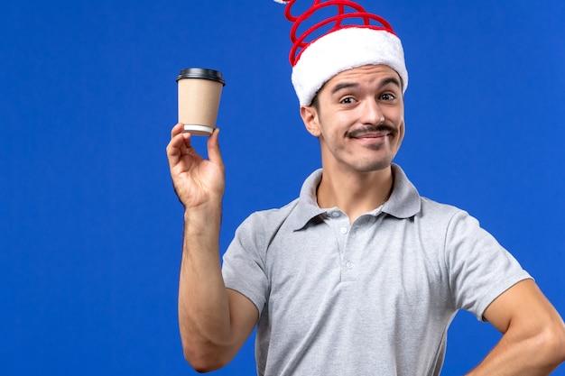 Vue de face jeune homme tenant une tasse de café en plastique sur le fond bleu nouvel an vacances masculines