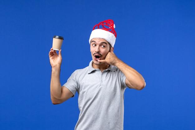 Vue de face jeune homme tenant une tasse de café en plastique sur mur bleu mâle vacances de nouvel an