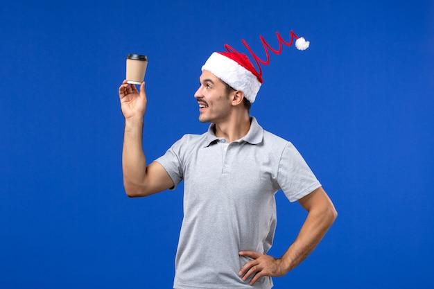 Vue de face jeune homme tenant une tasse de café en plastique sur le mur bleu nouvel an vacances masculines