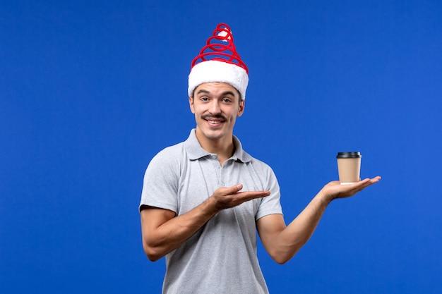 Vue de face jeune homme tenant une tasse de café en plastique sur mur bleu vacances mâle nouvel an