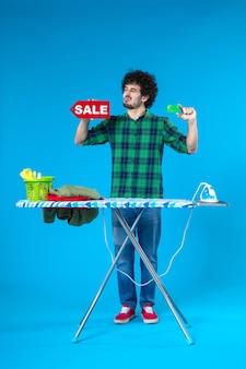 Vue de face jeune homme tenant vente écriture et carte bancaire sur fond bleu maison argent machine à laver propre shopping blanchisserie