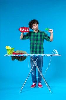 Vue de face jeune homme tenant vente écriture et carte bancaire sur fond bleu maison argent machine à laver propre shopping ménage blanchisserie