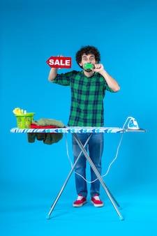 Vue de face jeune homme tenant vente écriture et carte bancaire sur fond bleu maison argent machine à laver shopping ménage blanchisserie propre