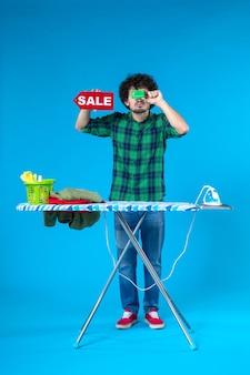 Vue de face jeune homme tenant vente écriture et carte bancaire sur fond bleu maison argent machine à laver travaux ménagers blanchisserie propre