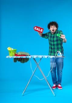 Vue de face jeune homme tenant vente écriture et carte bancaire sur fond bleu maison argent machine à laver travaux ménagers blanchisserie shopping propre