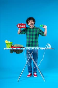 Vue de face jeune homme tenant vente écriture et carte bancaire sur fond bleu maison argent machine à laver travaux ménagers lessive propre