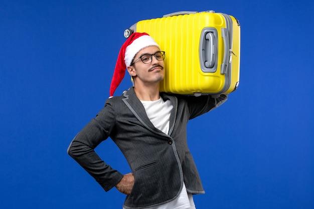Vue de face jeune homme transportant un lourd sac jaune sur le mur bleu vols avions vacances