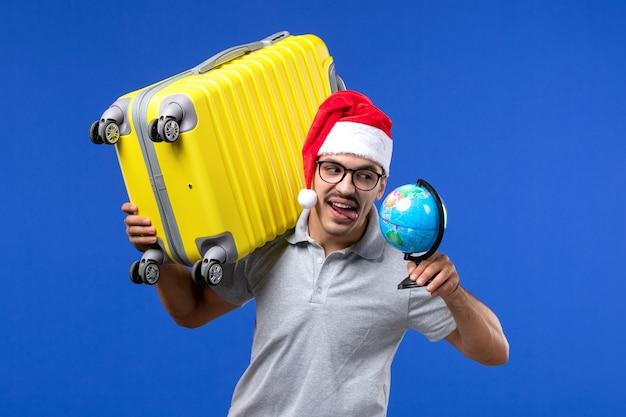 Vue de face jeune homme transportant un sac jaune sur les avions mur bleu voyage de vacances mâle