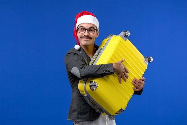 Vue de face jeune homme transportant un sac jaune lourd sur les avions de vol mur bleu vacances