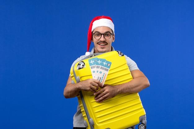 Vue de face jeune homme transportant un sac lourd avec des billets sur les avions de vacances vol mur bleu