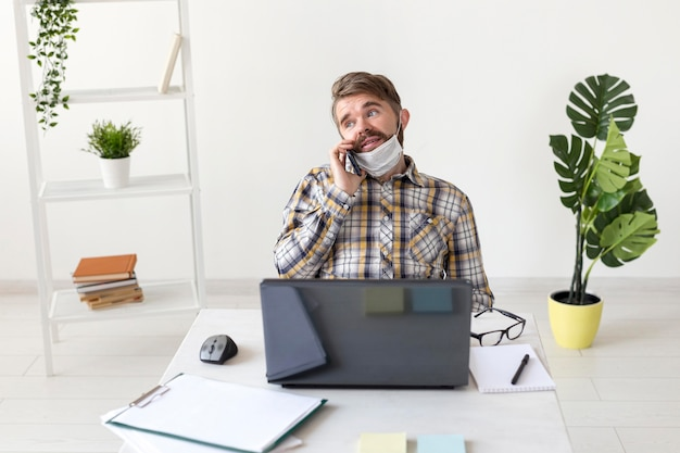 Vue de face jeune homme travaillant à domicile