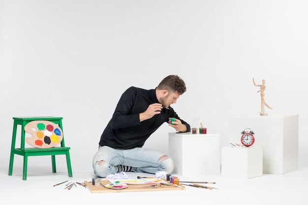 Vue de face jeune homme travaillant avec des peintures à l'intérieur de petites boîtes sur mur blanc artiste peinture art couleur peinture photo tirage photo