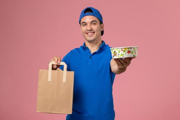 Vue de face jeune homme en uniforme bleu et cape avec colis de livraison et bol sur ses mains sur le mur rose