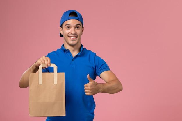 Vue de face jeune homme en uniforme bleu et cape avec colis de livraison de papier sur ses mains sur mur rose