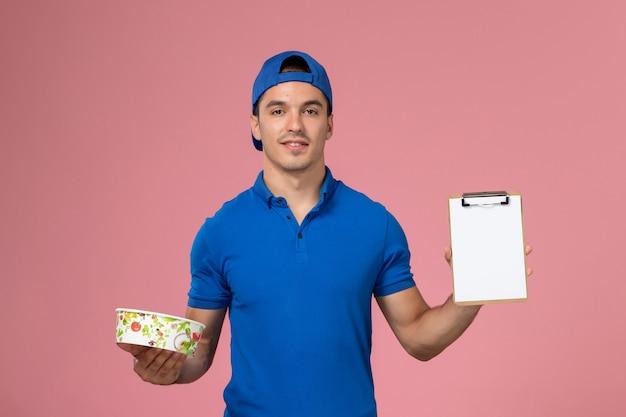 Vue de face jeune homme en uniforme bleu cape holding bloc-notes et bol de livraison rond sur le mur rose clair