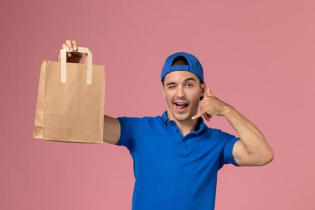Vue de face jeune homme en uniforme bleu et cape avec paquet de papier de livraison sur ses mains sur le mur rose