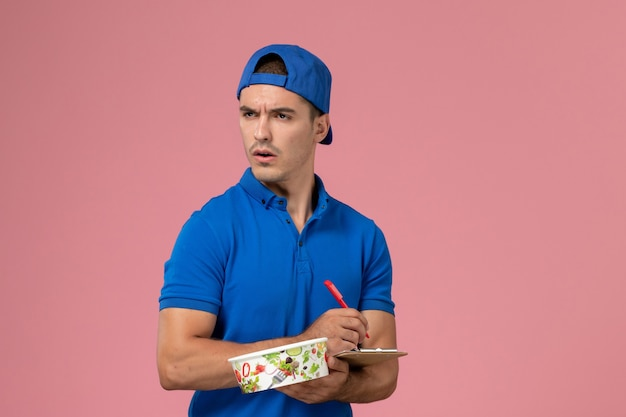 Vue de face jeune homme en uniforme bleu cape tenant le bloc-notes et bol de livraison rond écrit des notes sur le mur rose clair