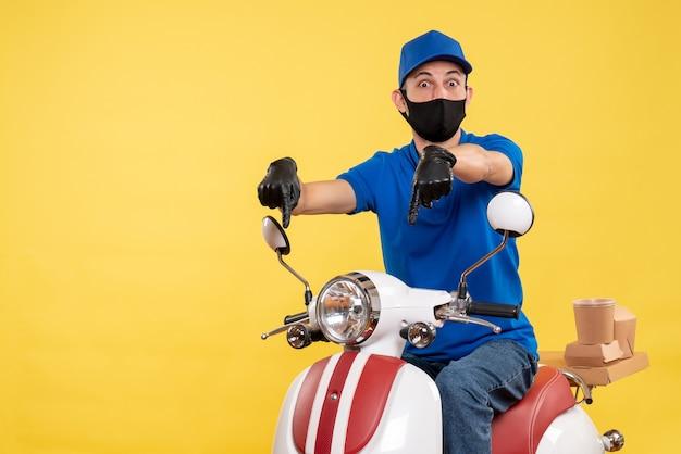 Vue de face jeune homme en uniforme bleu sur fond jaune bike covid- service pandémique virus travail de livraison de travail