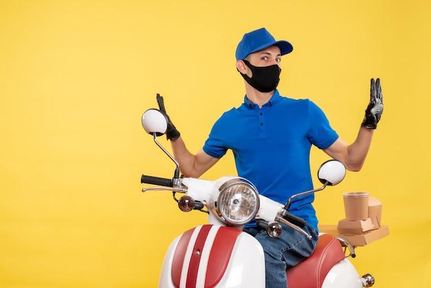 Vue de face jeune homme en uniforme bleu sur fond jaune covid- emploi service de livraison pandémique virus vélo travail