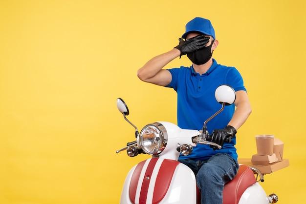 Vue de face jeune homme en uniforme bleu sur fond jaune covid- pandemic service job virus travail vélo