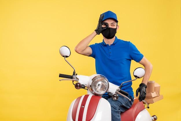 Vue de face jeune homme en uniforme bleu sur fond jaune covid- travail de travail de vélo de virus de livraison pandémique
