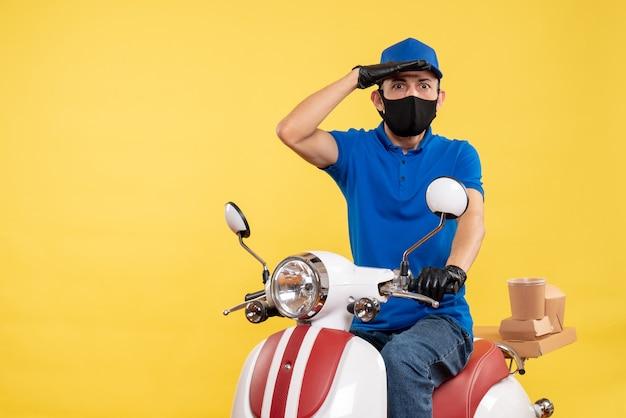 Vue de face jeune homme en uniforme bleu à la recherche sur fond jaune