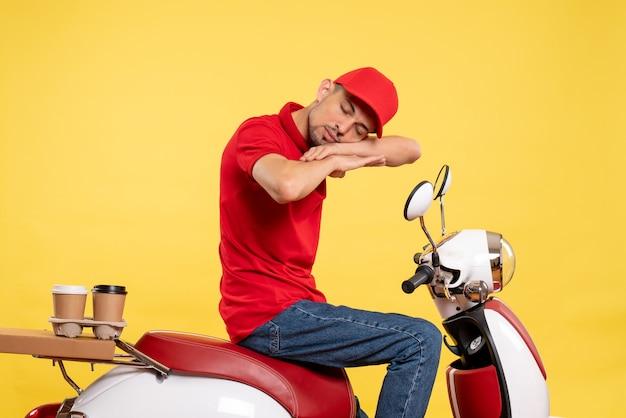 Vue de face jeune homme en uniforme rouge sur fond jaune