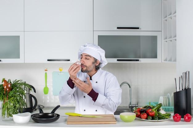 Vue de face jeune homme en uniforme sentant l'ail dans la cuisine