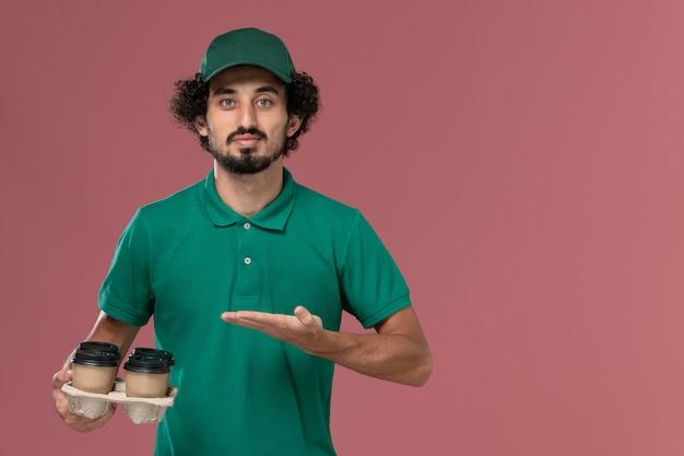 Vue de face jeune homme en uniforme vert et cape tenant des tasses de café de livraison marron sur le travail de travailleur de livraison uniforme de service fond rose clair
