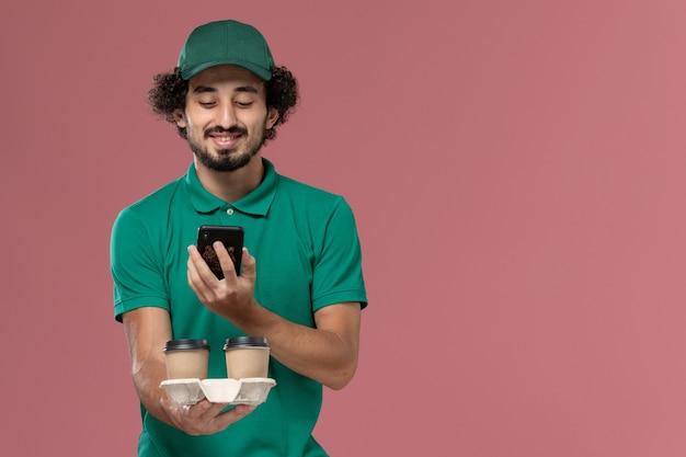 Vue de face jeune homme en uniforme vert et cape tenant des tasses de café de livraison en prenant une photo d'eux sur le travail de service de fond rose travailleur de la livraison uniforme