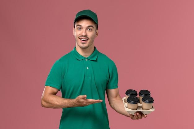 Vue de face jeune homme en uniforme vert tenant des tasses de café brun souriant sur fond rose clair