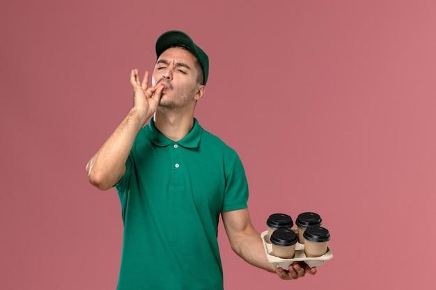 Vue de face jeune homme en uniforme vert tenant des tasses de café marron sur fond rose clair